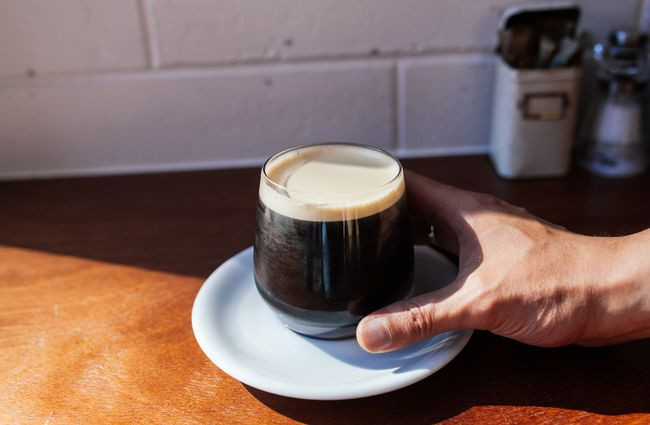 A hand holding a cup of nitro coffee.