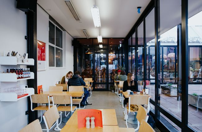 Cafe interior with large windows and plywood tables.