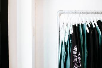 Green and black clothing on a rack.