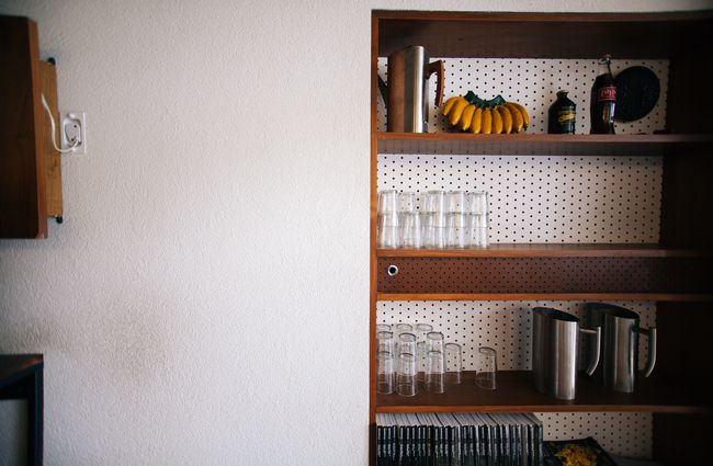 Interior shelving with dotty wallpaper.