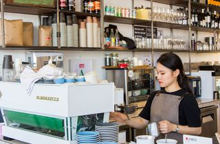Barista behind bar making coffee.
