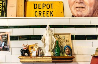 Shelf in front of white tiles and a yellow depot sign.