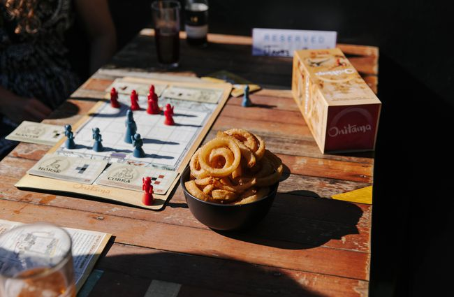Close up of a bowl of onion rings next to board game.