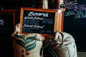 Blackboard sign on top of bags of beans.