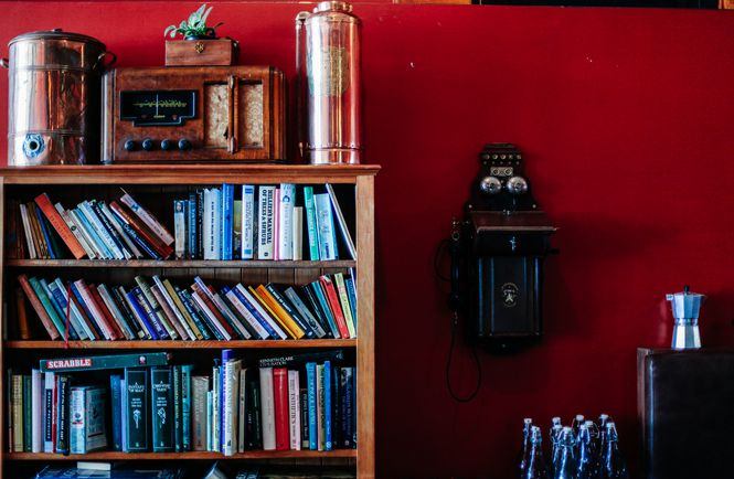 Bookshelf against a red wall.