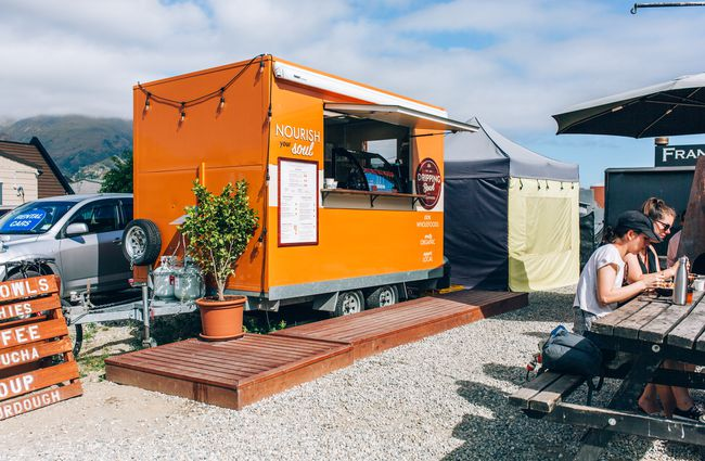 Orange caravan with a deck out the front.