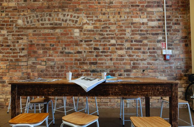 Wooden table inside by a brick wall.