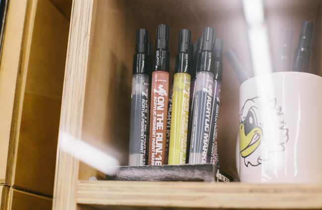 Paint markers on a shelf.