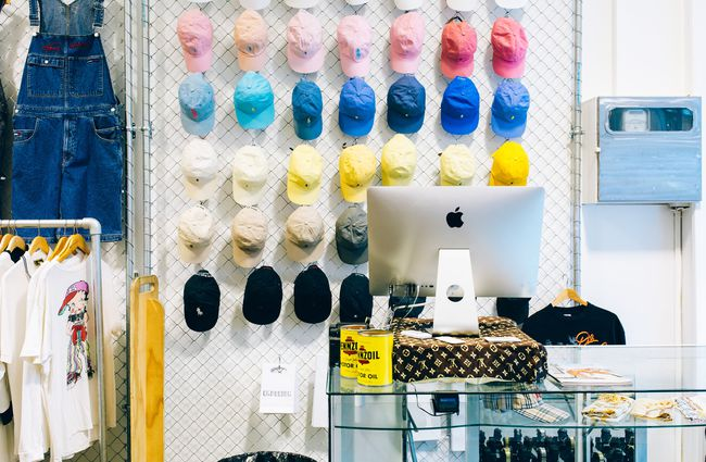 Coloured hats hanging from wall behind front counter.