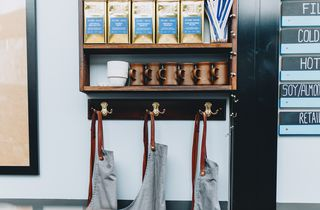 Aprons hanging on a wall alonside containers of tea at Engine Coffee Brewers cafe in Christchurch.
