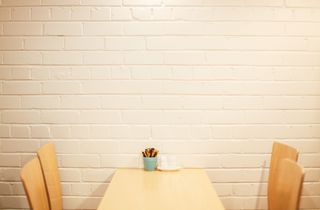Light wooden tables in front of a white brick wall.