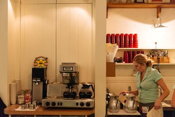 Waitress pouring water by coffee machine.