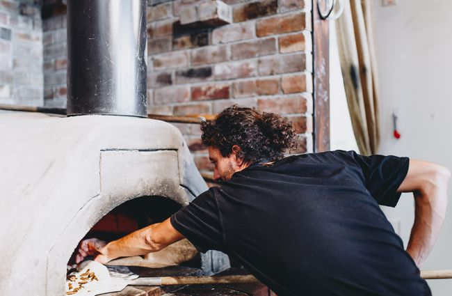 A chef putting a pizza in the wood fired oven in the kitchen at Francesca's Italian Kitchen, Christchurch.
