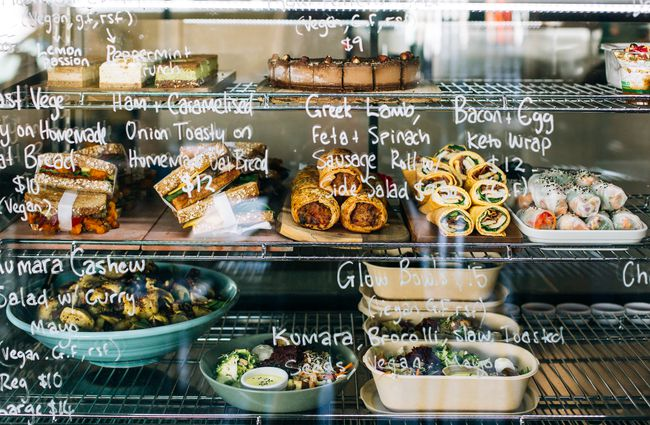 Glass cabinet full of food with white writing on glass.