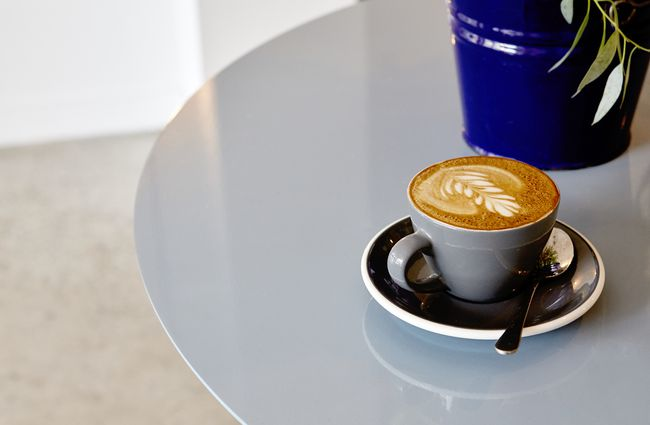 A flat white on a table inside Frank's Newtown cafe in Newtown Wellington.