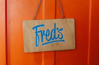 d500f86daf8b Blue Fred s sign against orange wall.