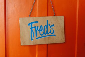 Blue Fred's sign against orange wall.