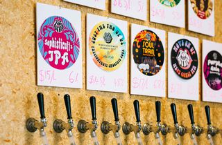 Taps and badges on a chipboard wall.