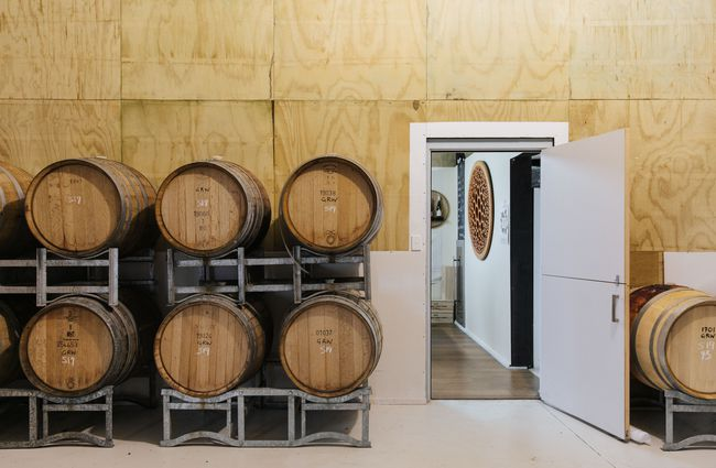 Inside the tasting room with wine barrels stacked on top of each other.