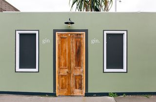 A green wall with a wooden door.