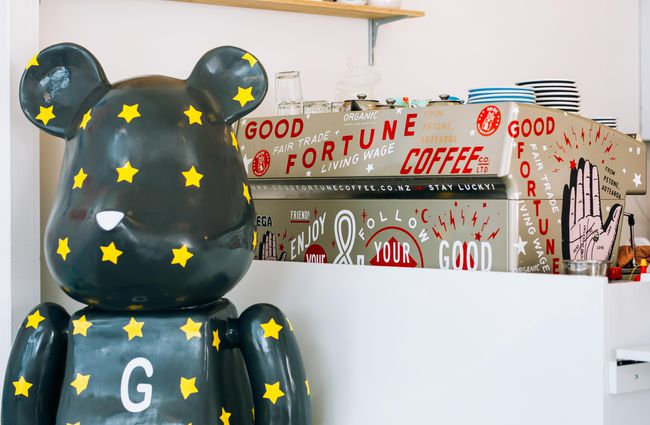 Black cat sculpture with yellow stars and a coffee machine with stickers.