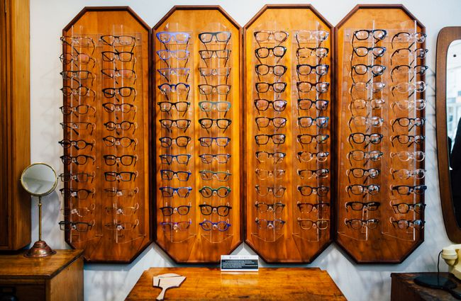 Wall of glasses on wooden stands.