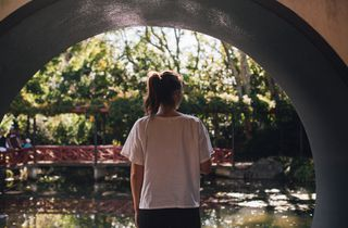 Woman looks out at gardens from tunnel.