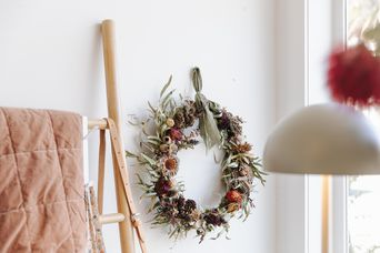 Dried flower wreath hanging on wall.