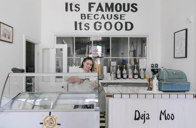 Woman behind counter making an ice cream cone.