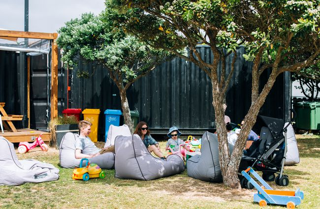 People sitting on grey beanbags under trees.