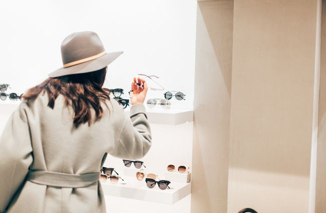 A woman looking at glasses.