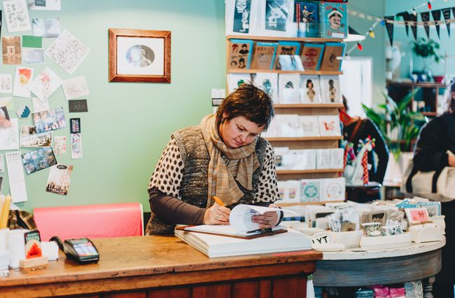 A woman working behind the counter at Henry Trading shop Lyttelton, Christchurch.