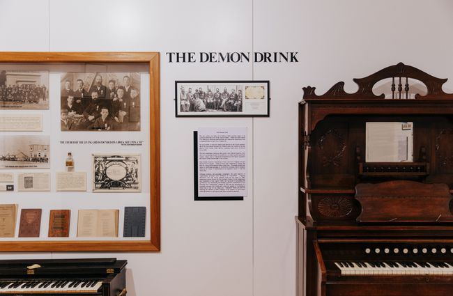 An exhibition of moonshine featuring a piano and signage.