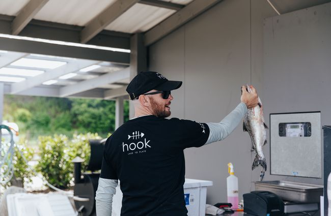 A chef holding up a large fish.