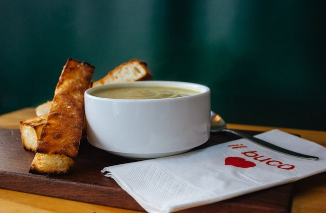 Green soup in a white bowl by bread.