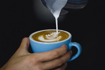 Pouring milk into coffee.