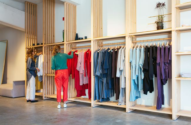Two women browsing through racks inside Kowtow Wellington clothing store, New Zealand.