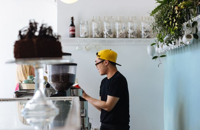 Barista in a yellow hat making coffee.