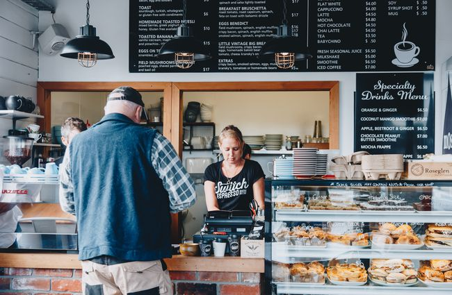 A woman serving a customer behind the counter at Little Vintage Espresso cafe Amberley, North Canterbury.