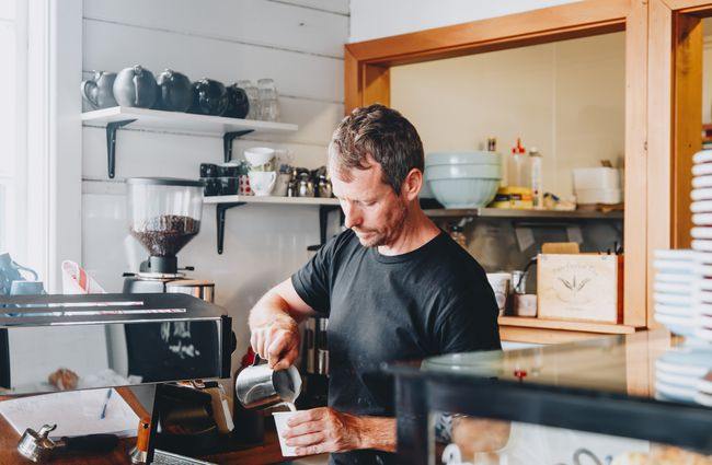 A barista pouring coffee behind the counter at Little Vintage Espresso cafe Amberley, North Canterbury.