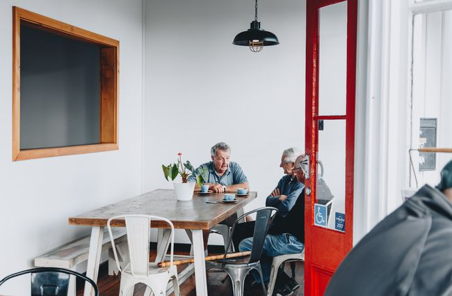 Three older men chatting around a table inside Little Vintage Espresso cafe Amberley, North Canterbury.