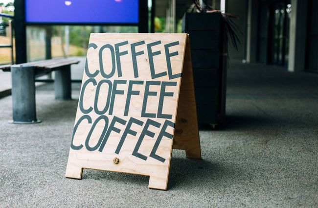 Coffee signs outside on the pavement.