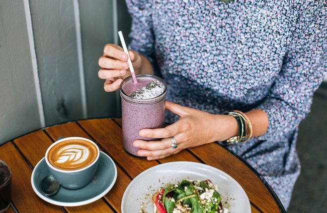 Woman drinking purple smoothie.