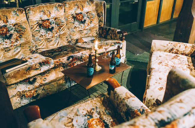 Vintage couches surrounding a table with empty beer bottles on it.
