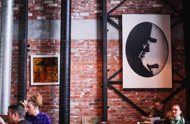 Two pieces of art on a brick wall inside Lyttelton Coffee Company cafe.