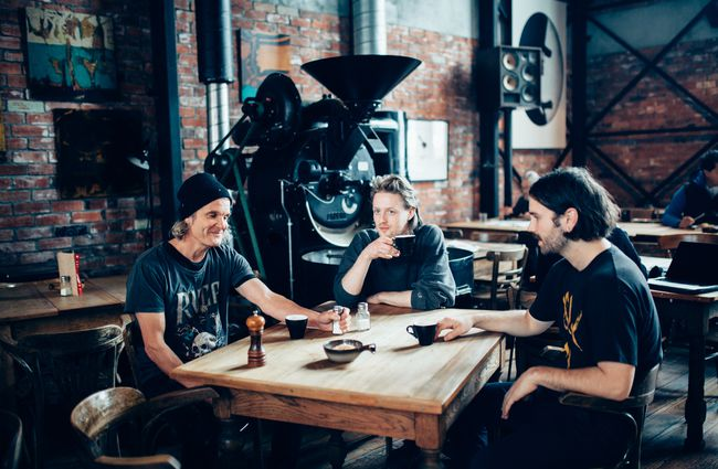 Three men drinking coffee around a table at Lyttelton Coffee Company.
