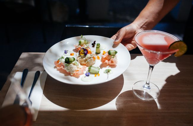 A pink cocktail in a martini glass and a colourful seafood dish.