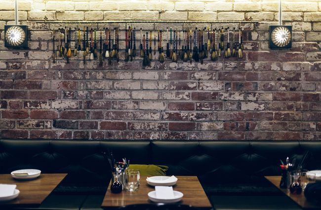 Exposed brick wall with black leather booth seating.