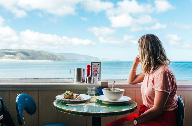 A woman looking out towards the ocean from a seat inside Maranui cafe Wellington.