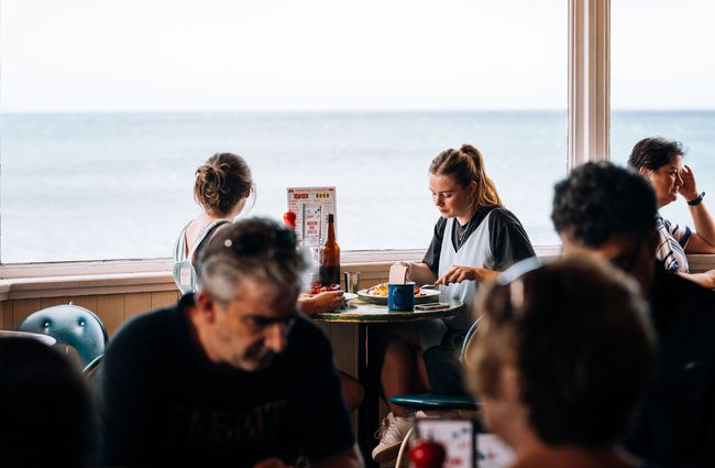 People dining by a large window inside Maranui cafe Wellington.